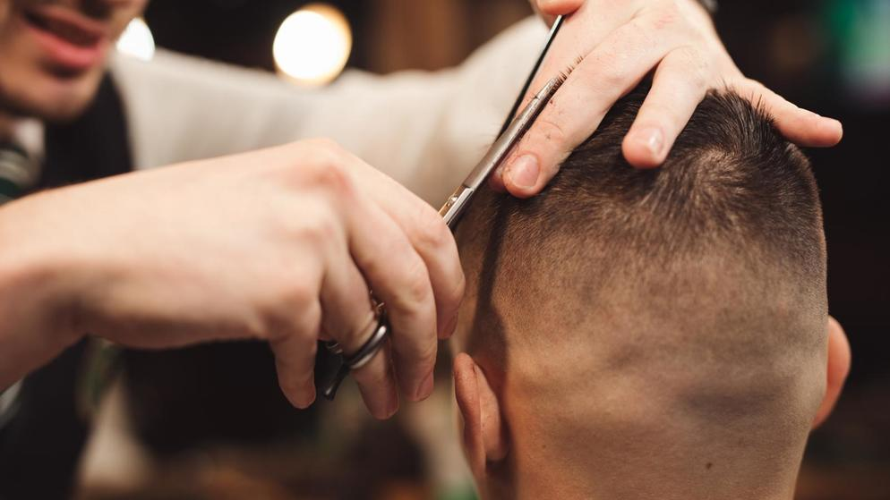 Professional haircut with scissor in a male barbershop salon
